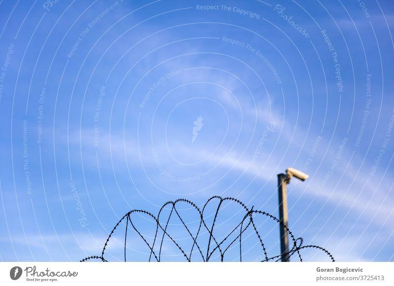 Sicherheitskamera hinter Stacheldrahtzaun an der Gefängnismauer Gefahr Borte Himmel Lager Draht Rasierer mit Stacheln versehen Schutz Verbrechen Überwachung