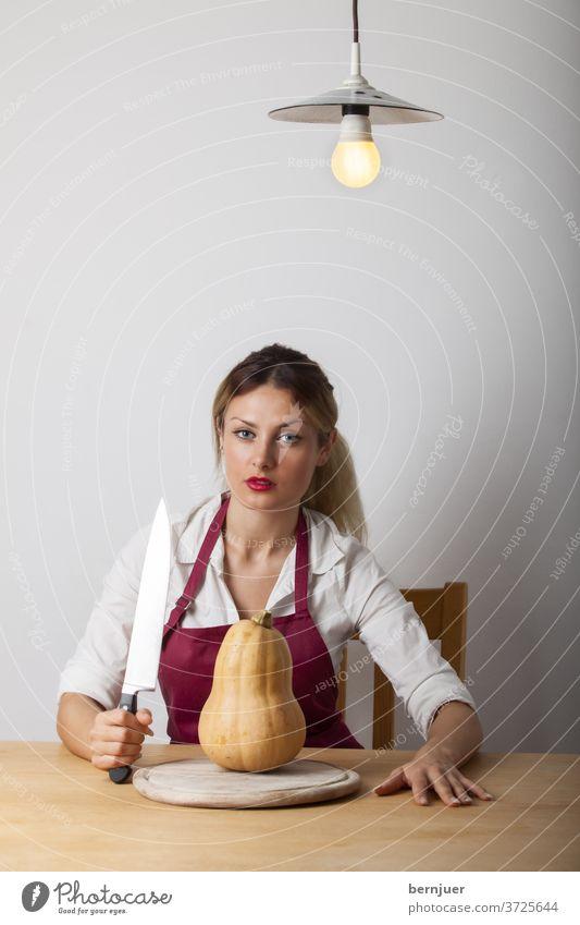 Frau mit Kürbis Kochmesser Essen Gemüse orange Mahlzeit Abendessen Küche halten Schürze jung Tisch Frühstück orange Farbe Küche Arbeitsplatte gesund Ernährung