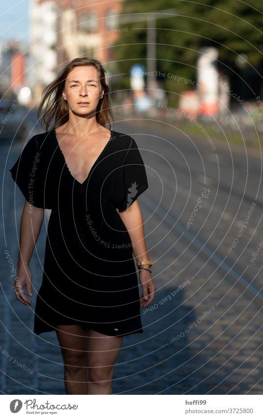 die Frau geht, den Blick ihn die Kamera gerichtet, elegant und selbstbewusst die Strasse herunter. feminin Junge Frau 18-30 Jahre langes Haar Haare & Frisuren