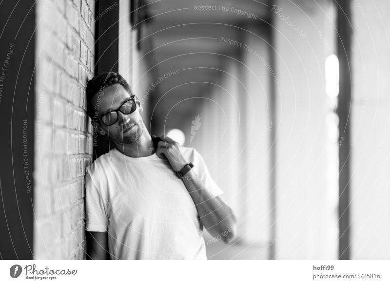 Der junge Mann mit Sonnenbrille lehnt lässig an einer Wand und schaut in die Kamera Junger Mann Maskulinität schön Mannlich Gesicht portraite Denken