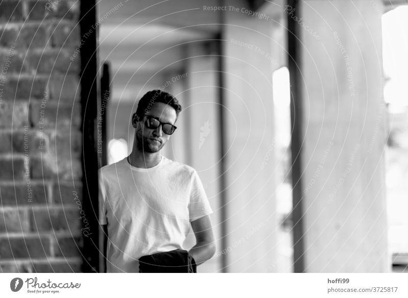 Der junge Mann mit Sonnenbrille schaut in die Kamera Junger Mann Maskulinität schön Mannlich Gesicht portraite Denken Schwarzweißfoto Männergesicht