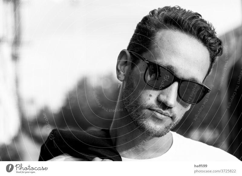 der Mann mit Sonnenbrille trägt lässig sein Sakko über der Schulter Porträt maskulin Coolness trendy Erwachsene Kopf Blick nach vorn selbstbewußt ästhetisch