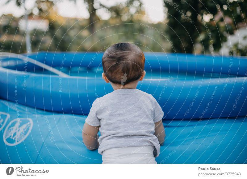 Kleinkind auf dem Pool Beckenrand aufblasbar Sommer Sommerurlaub Kind Baby 0-12 Monate Sicherheit sicher gefährlich Spielen schön Außenaufnahme Tag niedlich