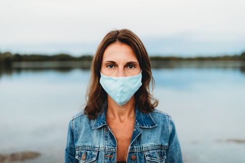 Frau trägt Mundschutz in der Corona Pandemie Maske Gesichtsmaske Schutz Coronavirus covid-19 COVID Virus Infektionsgefahr Corona-Virus Prävention Krankheit