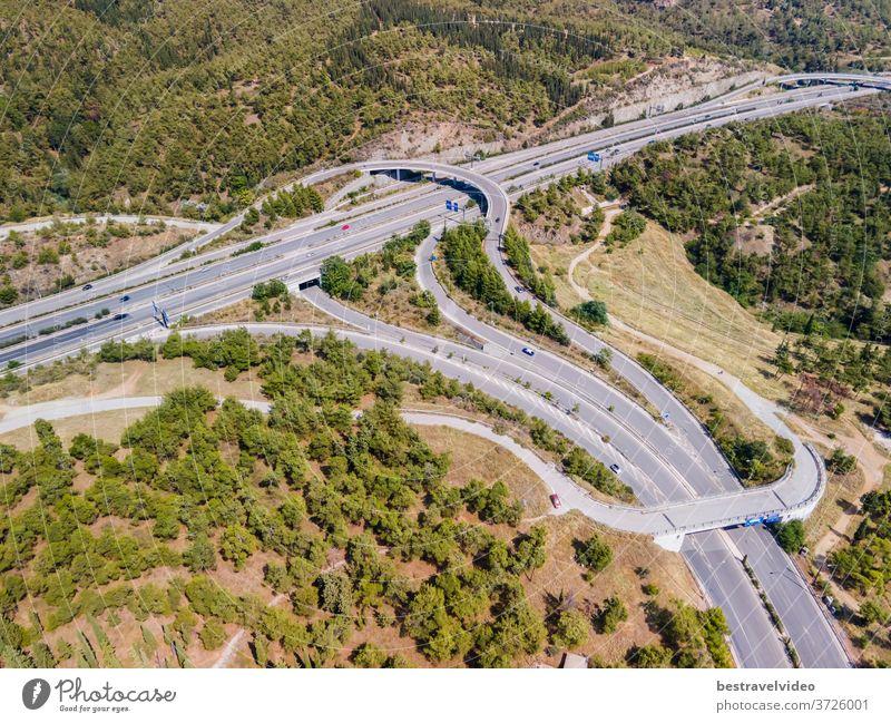 Thessaloniki, Griechenland: Drohnenlandschaft des Kreuzungsverkehrs auf der inneren Ringstraße Periferiaki. Tagesspitzenpanorama eines europäischen Mehrebenen-Stapelautobahnkreuzes mit vorbeifahrenden Autos durch Wald.