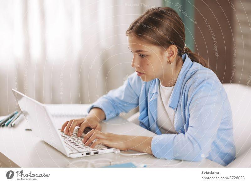 Teenager-Mädchen mit Kopfhörern am Tisch sitzend und Hausaufgaben per Videokonferenz mit Laptop machen, Online-Bildung, Fernunterricht, Technologiekonzept