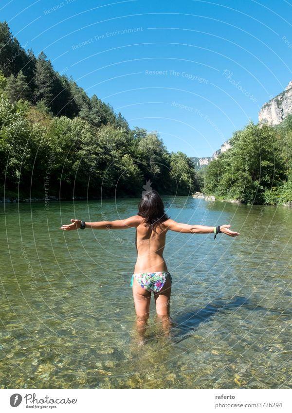 Rückansicht einer Frau mit erhobenen Armen, die beim Baden in den Fluss steht 1 Wasser nass jung Erwachsener Arme hochgezogen Behaarung schön Schönheit Mädchen