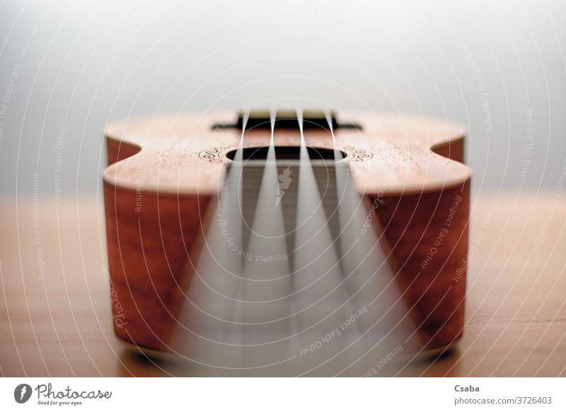 Braune Ukulele auf Holzgrund mit geringer Feldtiefe Instrument akustisch Musik braun hölzern Hintergrund Gitarre Musical Schnur Rosette hawaiianisch Objekt