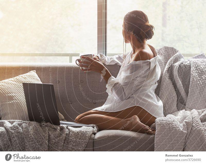 Schöne und sexy junge Frau, die einen Laptop benutzt, während sie auf dem Sofa sitzt Fenster einer Luxuswohnung. Stil blond Innenbereich Unschuld brünett