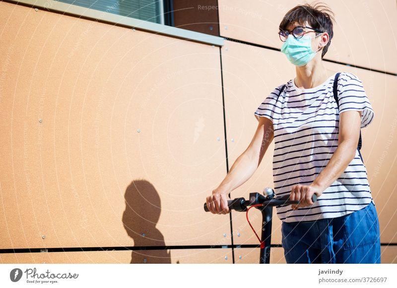 Frau fährt auf einem Elektroroller durch die Stadt Tretroller elektrisch Mädchen Mundschutz Öko Transport urban Lifestyle modern Freizeit Großstadt