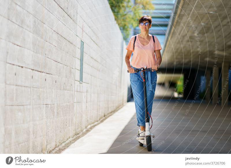 Frau fährt auf einem Elektroroller durch die Stadt Tretroller elektrisch Mädchen Öko Transport urban Lifestyle modern Freizeit Großstadt Mitfahrgelegenheit