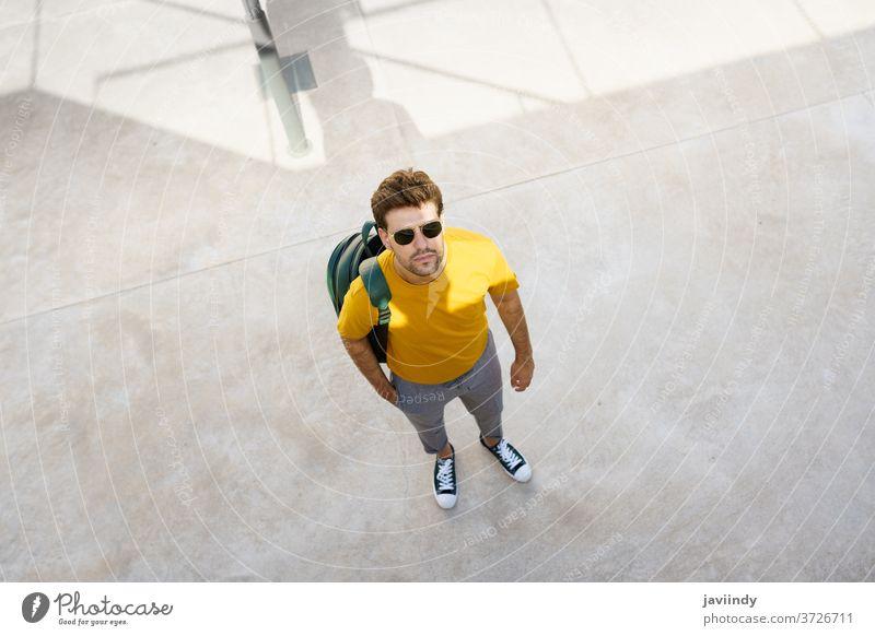 Draufsicht auf einen männlichen Studenten auf dem Universitätscampus. Mann urban Schüler jung Rucksack Lifestyle Stil Person Kaukasier Typ lässig Straße
