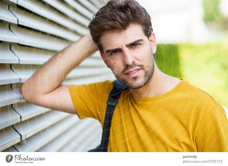 Junger Mann mit modernem Haarschnitt im städtischen Hintergrund männlich Frisur Schüler urban Lifestyle cool Person lässig Erwachsener jung im Freien Straße