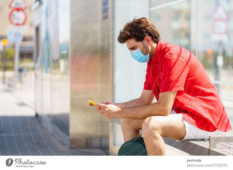 Junger Mann trägt eine chirurgische Maske, während er an einem Außenbahnhof auf einen Zug wartet Schüler Mundschutz Tourismus Ökomobilität Reisender jung