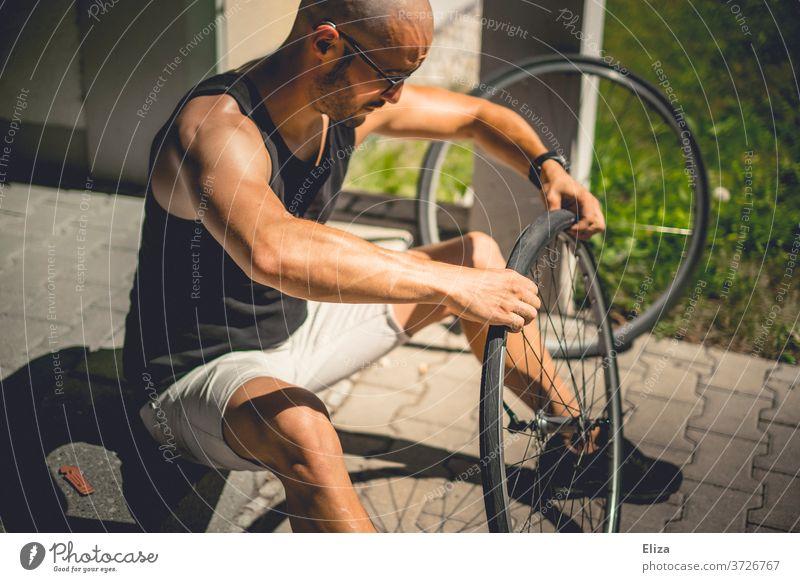Ein Mann sitzt draußen in der Sonne und zieht einen Fahrradmantel auf das Laufrad seines Fahrrads, nachdem er den Schlauch geflickt hat reparieren Mantel