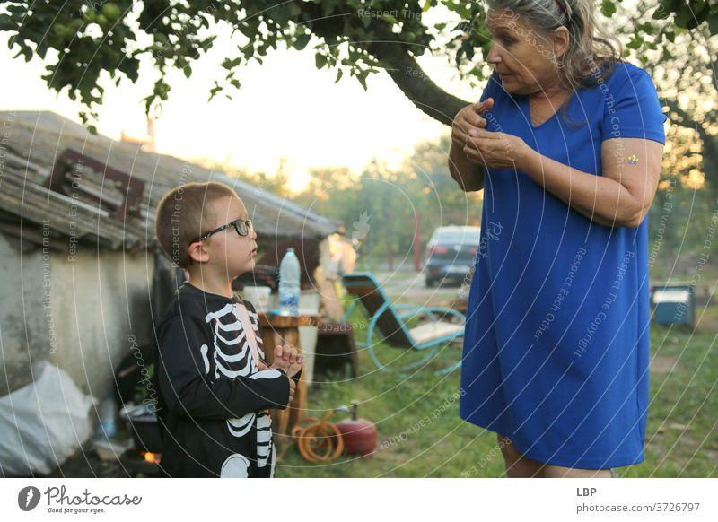 Frau spricht mit Kind, das ein Skelettkostüm trägt Porträt Liebe Wahrheit Vertrauen Gefühle Leben Kindheit Paar Familie & Verwandtschaft Großmutter Senior