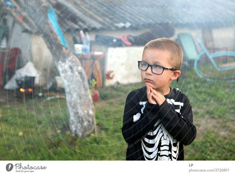 Junge, der ein Skelettkostüm trägt und auf etwas achtet Wunder erstaunt Gebet Glaube und Religion fassungslos Christentum Gott Hoffnung Spiritualität beten