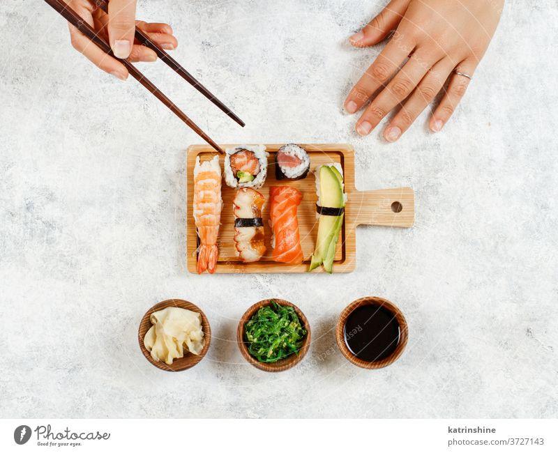 Draufsicht auf die Hand, die mit Stäbchen eine Rolle nimmt Sushi unter Essstäbchen verzehrfertig Essen Sashimi Brötchen Sushi-Bar Esszimmer Japanisch Kultur