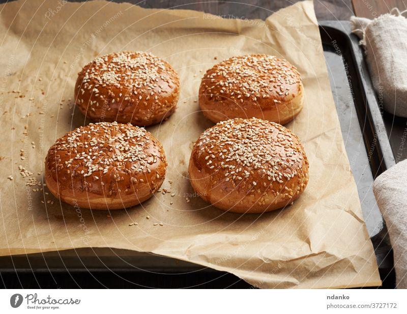 gebackene Sesambrötchen auf braunem Pergamentpapier, Zutat für einen Hamburger Brötchen Burger Cheeseburger klassisch Nahaufnahme Kruste lecker Bäckerei Brot