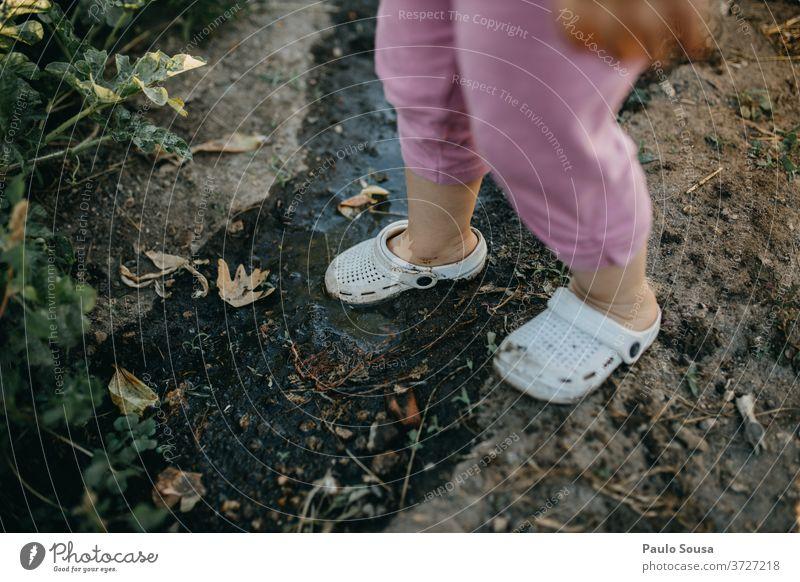 Kind mit Crocs auf dem Schlamm Gummi Krokodile Schuhe schlammig Komfortabel dreckig Farbfoto Natur Erde Tag Außenaufnahme braun Mensch Gummistiefel grün Pfütze