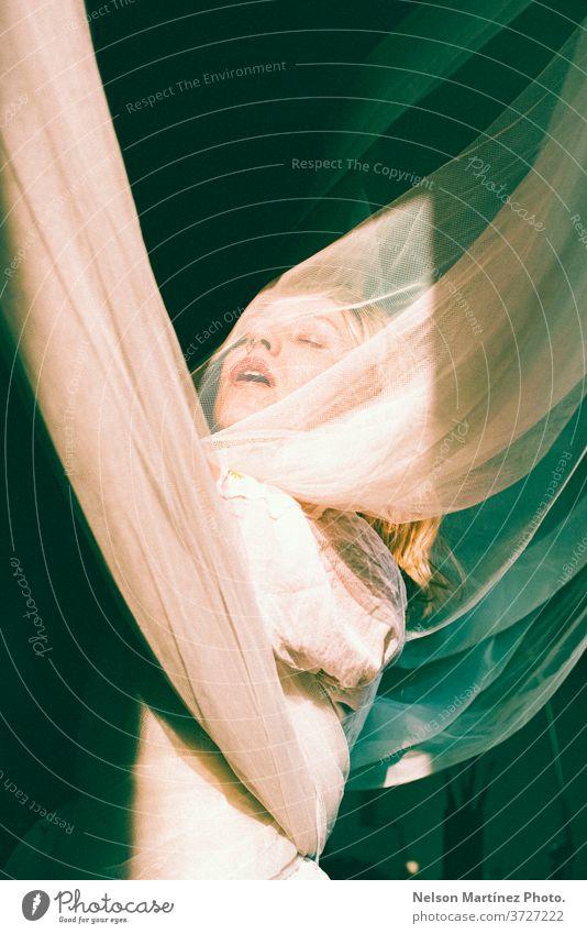 Porträt einer blonden Frau. Sie ist mit offenen Armen, in Tüllvorhänge gehüllt. bonde Künstler Kunst natürliches Licht Freiheit sinnlich Kaukasier hübsch jung