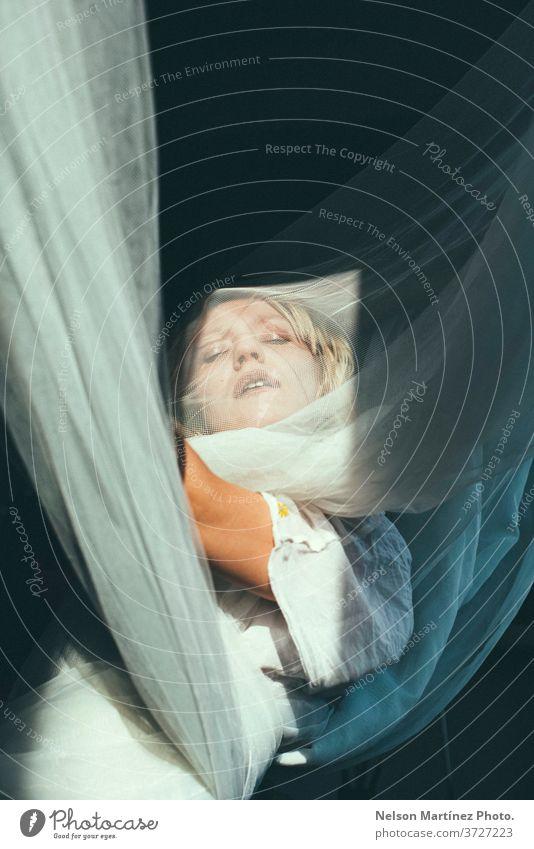 Porträt einer blonden Frau. Sie ist mit offenen Armen, in Tüllvorhänge gehüllt. träumend surrealistisch Eleganz hübsch schön Mensch Lifestyle Mode Blick feminin