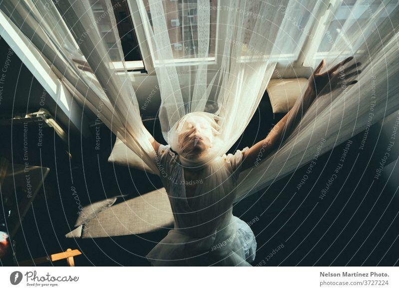 Überkopfporträt einer blonden Frau. Sie ist mit offenen Armen, in Tüllvorhänge gehüllt. Porträt tull Vorhänge natürliches Licht Kaukasier hübsch schön Blick