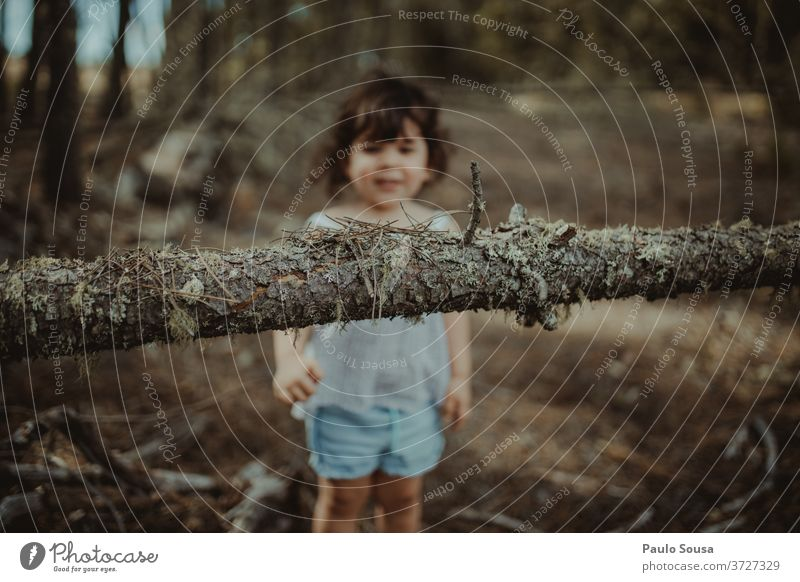 Kleines Mädchen spielt im Wald Kind Kinderspiel Kindheit Baumstamm Kofferraum Wälder Spaß haben Kleinkind Lifestyle Farbfoto Spielen Glück Außenaufnahme