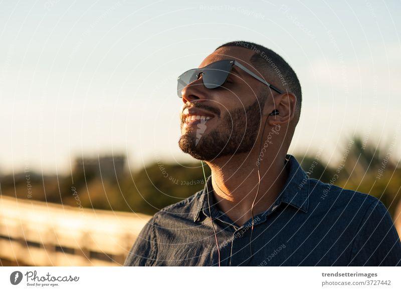 Lateinamerikaner, der über Kopfhörer Musik oder Motivationspodcasts hört und den Sonnenuntergang genießt Meditation Podcast Berghänge Urlaub Strand außerhalb