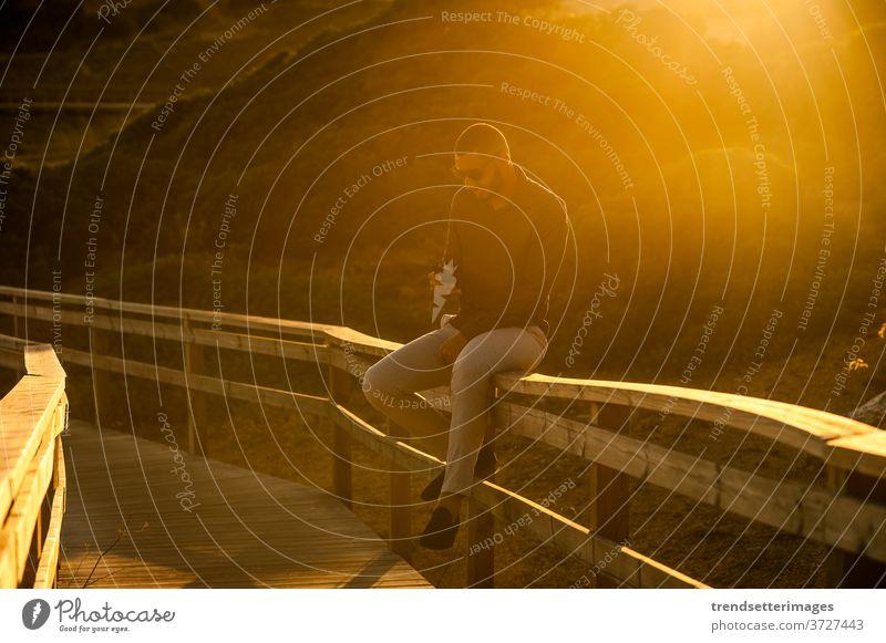 Lateinamerikanischer Mann nimmt sich mit einem Smartphone über eine erstaunliche Sonnenuntergangslandschaft Tourist Sommer Urlaub SMS außerhalb Stil hispanisch