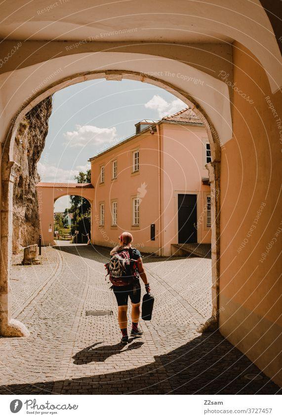 Junge Radfahrerin im Torbogen radfahrerin fahrrad reisen rucksack tasche sport sportlich sommer sonne himmel kloster weltenburg blond mädchen frau jung