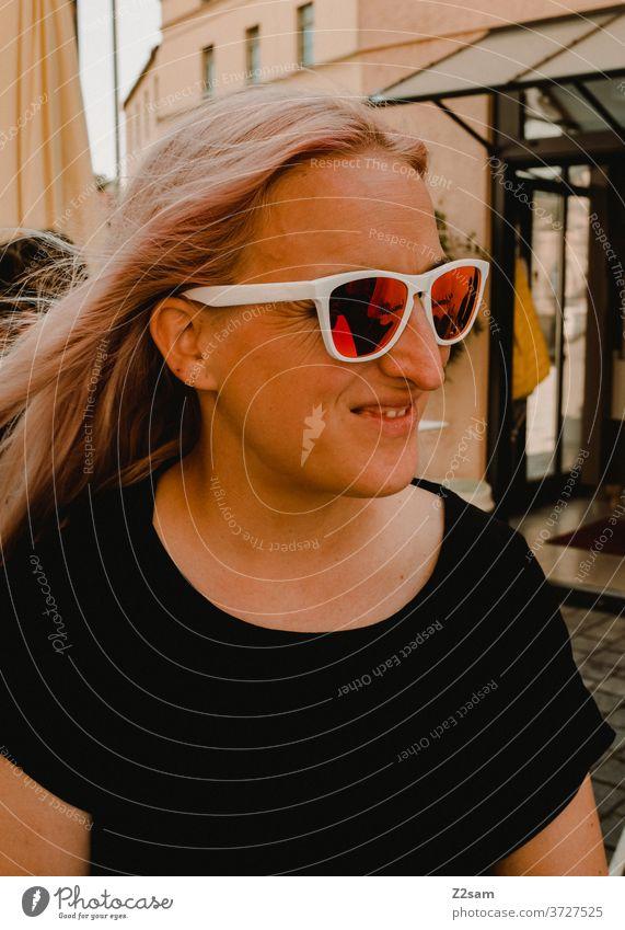 Junge Frau mit Sonnenbrille junge frau blond hübsch schön sonnebrille lachen lächeln glücklich zufrieden t-shirt schwarz innenstadt attraktiv Fröhlichkeit