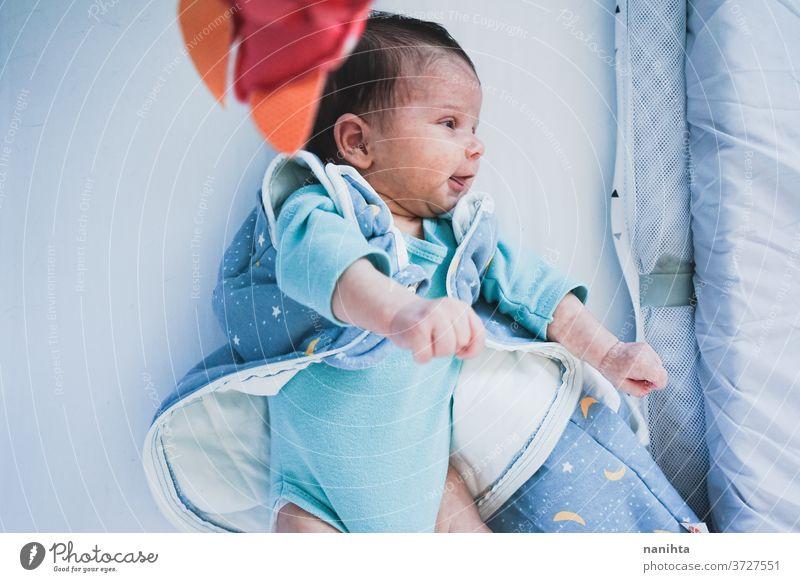 Liebliches und verspieltes Neugeborenes in ihrem Schlafzimmer zu Hause neugeboren spielerisch neugierig Baby lieblich niedlich unisex Kleidung Wiege Babybett