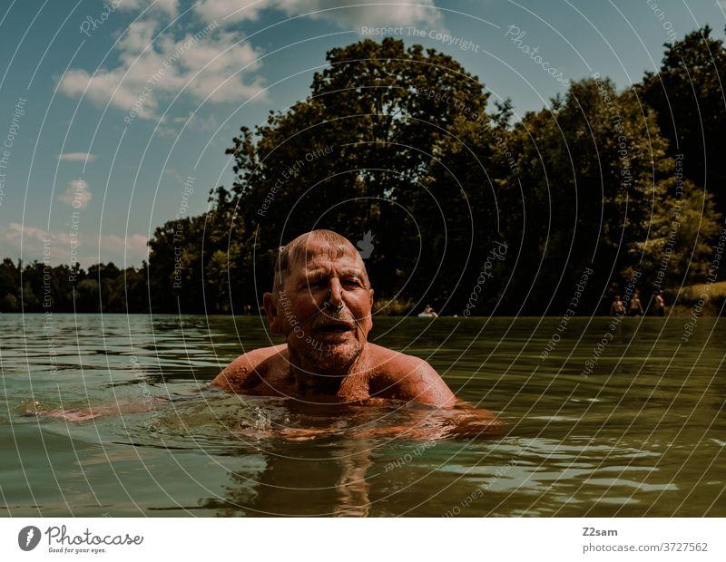 Rentner beim Schwimmen im See schwimmen freizeit rentner rente sommer see gewässer wasser sport bewegung nasenklammer sportlich braun alter mann portrait
