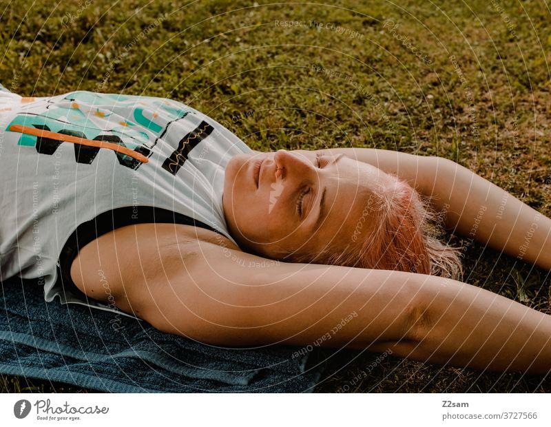Junge Frau relaxt in der Wiese entspannung frau ausruhen ausgleich sommer sonne wiese natur liegen träumen schlafen erholung jung weiblich sportlich joga arme