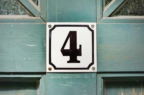 Die Zahl vier steht in schwarz und eingerahmt auf einem quadratischen Schild an der alten, blauen Holztür 4 Nummernschild Altbau Haustür Tür wohnen