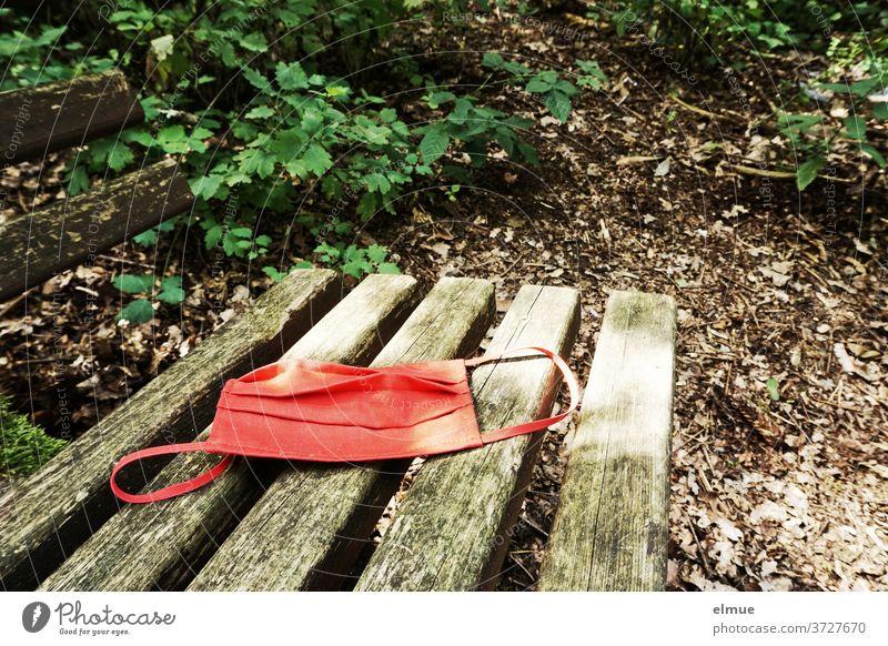 eine rote Nasen-Mundschutz-Maske liegt auf einer alten Holzbank im Wald Verweigerung Corona-Virus Infektionsgefahr Atemschutzmaske Schutzmaske Stoff Staoffmaske
