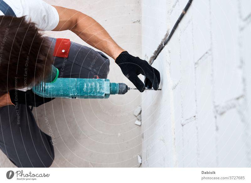Mann Arbeiter bohrt Wand mit Hammerbohrer, Draufsicht bohren Renovierung Reparaturen männlich Erwachsener Kraft Bohrung Werkzeug Beteiligung heimwärts Golfloch