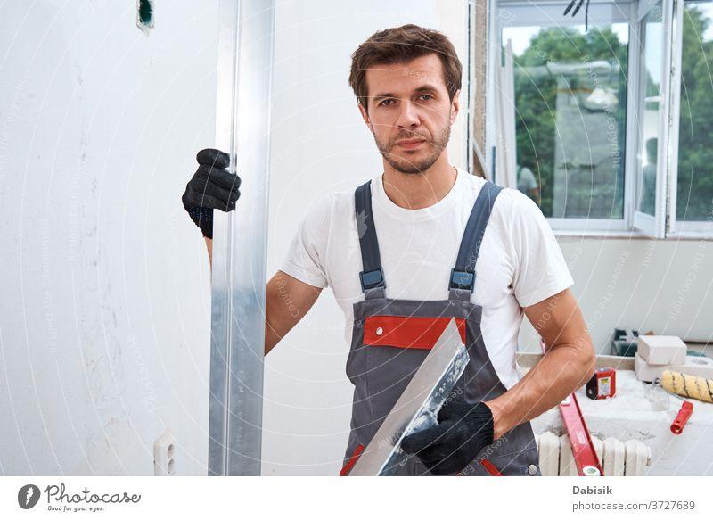 Renovierungskonzept. Männlicher Arbeiter verputzt eine Wand mit einem langen Spachtel verputzen Mann Werkzeug Stuck Industrie manuell Reparatur Konstruktion
