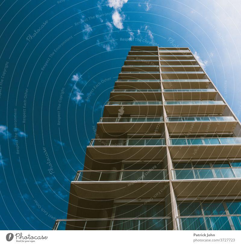 Hochhaus im blauem Himmel Sommer Bungalow Ferienwohnung Domizil Architektur Fassade Menschenleer modern Außenaufnahme Froschperspektive Fenster Glas