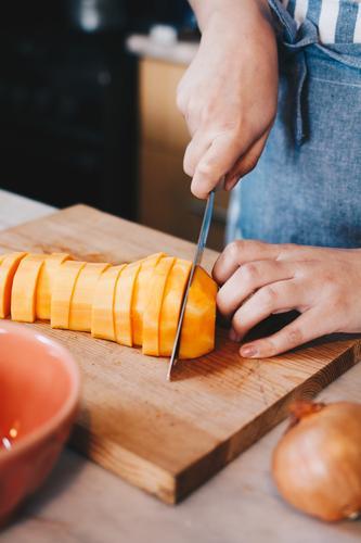 Butternusskürbis wird mit dem Kochmesser geschnitten Butternuss-Kürbis Lebensmittel Foodfotografie Food-Styling Essen und Trinken Vegane Ernährung Veganismus