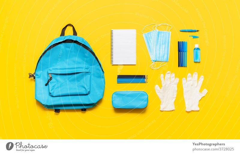 Schulsachen und Rucksack von oben gesehen. Zurück zur Schule bei Pandemie mit Schutzmasken Rücken zurück zur Schule Hintergrund blau Konzept Textfreiraum Korona