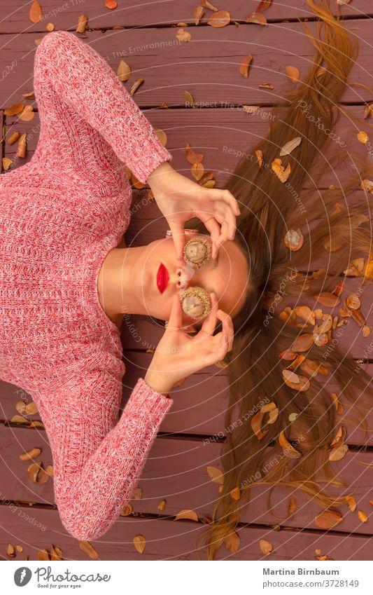 Wo ist der Herbst? Junge Frau, die auf einem Holzdeck liegt und ihre Augen mit riesigen Eicheln bedeckt. Spaß haben Model natürlich Gesicht Porträt Blatt