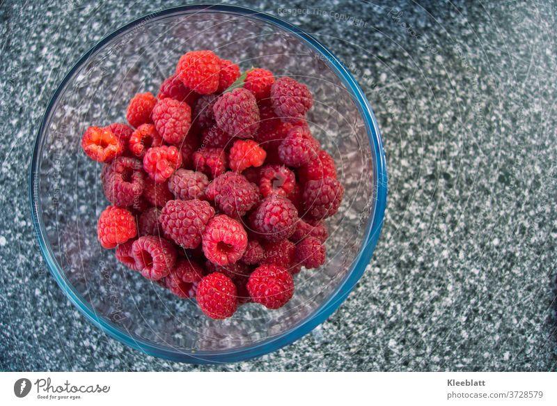 Himmbeeren frisch geerntet aus dem Biogarten angerichtet in einer Glasschale warten darauf vernascht zu werden Frisch Bioprodukte Lecker Rot