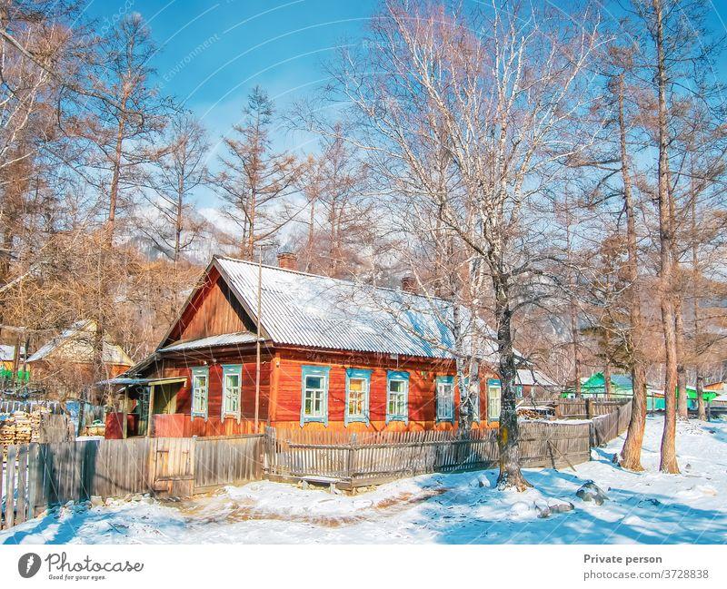 Malerisches Holzhaus im Wald an einem sonnigen Wintertag. Schnee, blauer Himmel, Berge im Hintergrund. Gesundes Lebenskonzept, ländliches Leben. Dorf weiß