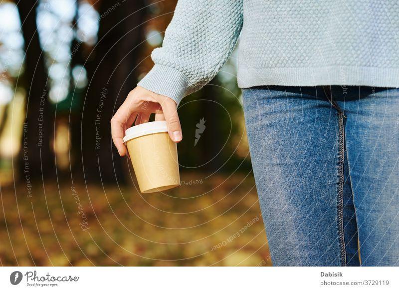 Frau hält Tasse Kaffee zum Mitnehmen im Herbstpark im Freien weg Tee trinken Einwegartikel Papier Hand gehen Sie heiß Morgen Latte Imbissbude Halt Beteiligung