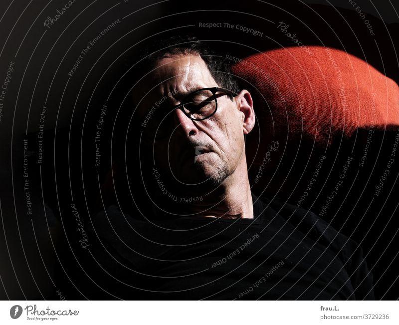 Im Sonnenlicht schlafend träumte der Mann von einem orangeroten Kissen, das sich an sein Ohr kuschelte Sofa sitzen Porträt Innenaufnahme Erholung Nickerchen