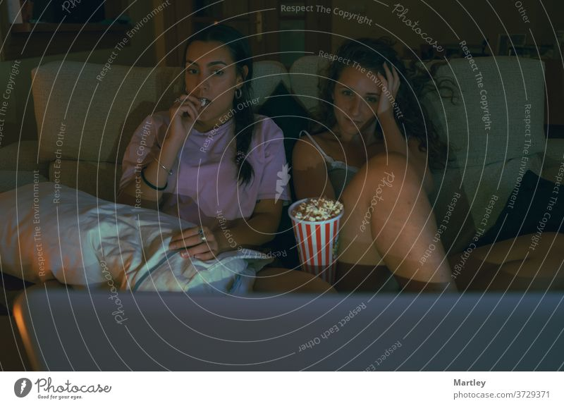 Zwei Teenager Mädchen essen Popcorn und schauen online einen Film an, während sie zusammen auf dem Sofa in einem gemütlichen Wohnzimmer sitzen. Popkorn