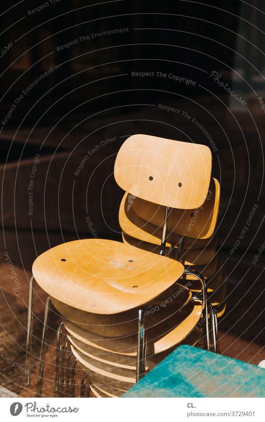 stapel stühle Stuhl Stuhlstapel Stapel Möbel Sitzgelegenheit ästhetisch Holz Stuhllehne dunkel platzsparend leer braun verlassen Metall ruhig viele Menschenleer