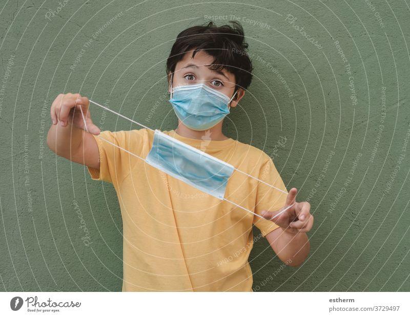 Kind mit medizinischer Maske, das eine medizinische Schutzmaske hält Coronavirus Virus medizinische Maske Seuche Pandemie Quarantäne covid-19 Symptom Medizin